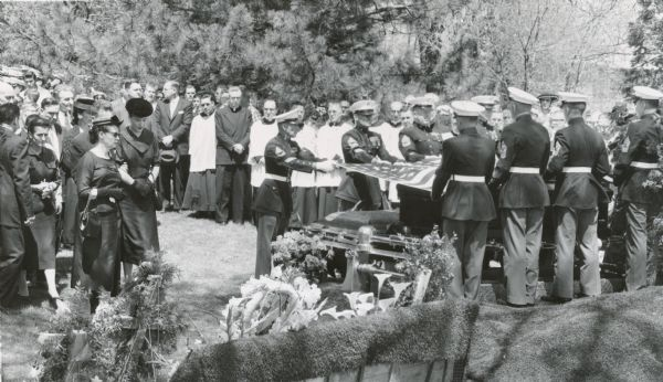 Marine honor guard at the funeral of Senator Joseph R. McCarthy.  Jean McCarthy (wearing a round black hat), stands to the left of the Marines. McCarthy's death created a virtual frenzy among Wisconsin political leaders — both Republicans and Democrats — for election to the senator's unexpired seat. Ultimately Democrat William Proxmire won in a surprise victory that attracted national attention.