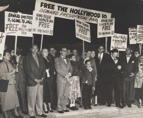 "Several members of the screenwriters and directors known as the ""Hollywood Ten,"" together with members of their families at a demonstration before their imprisonment for failure to testify before the House Un-American Activities Committee about their Communist Party memberships or associations. Included second from the left are Albert Maltz, Alvah Bessie (in the beret), and Dalton Trumbo (wearing eyeglasses). Herbert Biberman is third from the right and Ring Lardner, Jr., is standing under the Adrian Scott sign. Public concern that Communist sympathizers might be including propaganda in Hollywood films was part of the background to the anti-Communist hysteria created by Joseph R. McCarthy during the 1950s."