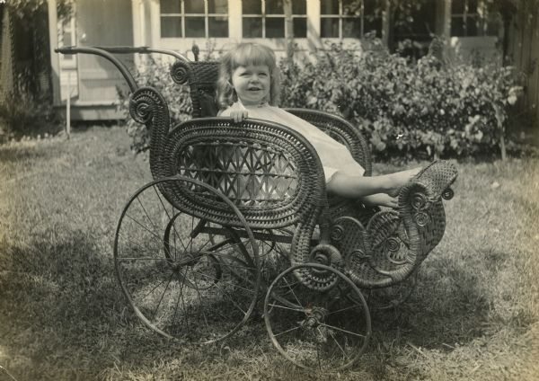 Agnes Moorehead is shown at about 4 years of age sitting in a handsome wicker baby carriage outdoors.