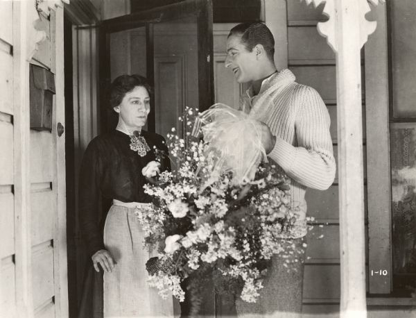 Publicity still from <i>The Blot</i>. Louis Calhern with flowers at the front door with Margaret McWade.  (Lois Weber Productions, 1921).