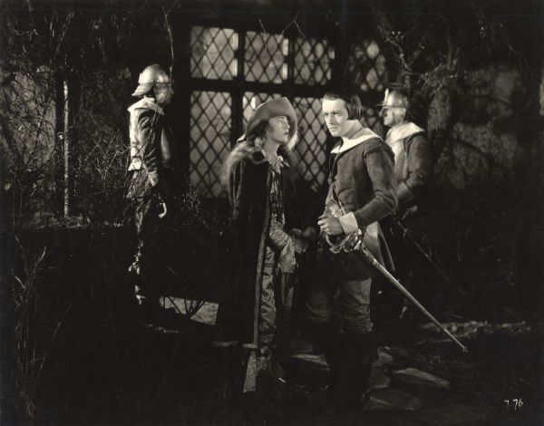 A scene still from <i>The Fighting Blade</i> with Richard Barthelmess and Dorothy Mackaill in the foreground and two helmeted guardsmen behind them.