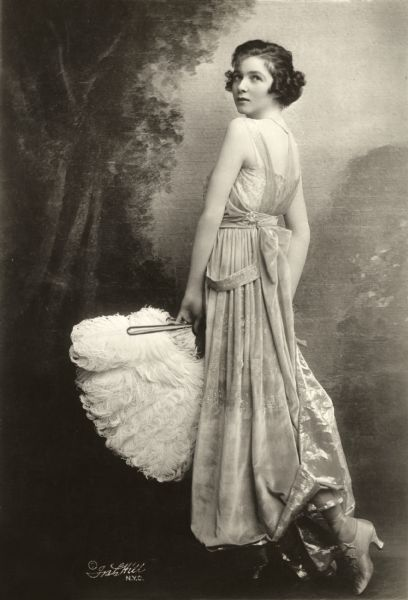 Full-length publicity portrait of Irene Castle posed in a studio in front of a painted backdrop. She looking over her shoulder at the camera and is wearing a light colored velveteen dress and holding a white ostrich feather fan.