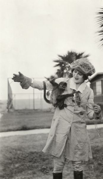 Silent film actress Ruth Roland in riding costume and a velveteen cap playing with a small monkey.