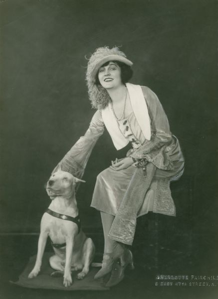 "Broadway actress Eleanor Woodruff, wearing a dress with flared sleeves, a feathered hat, and pearls, posed with a white bull terrier.  Original caption: ""Eleanor Woodruff in <i>Back to Methuselah,</i> Garrick Theatre."""