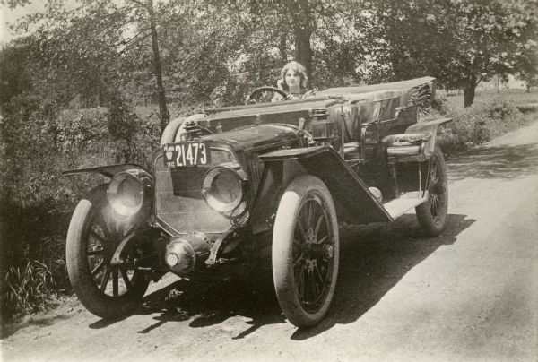 A publicity still of Victor Film Company silent film star Florence Lawrence driving a Lozier open touring car with 1912 Pennsylvania license plates.