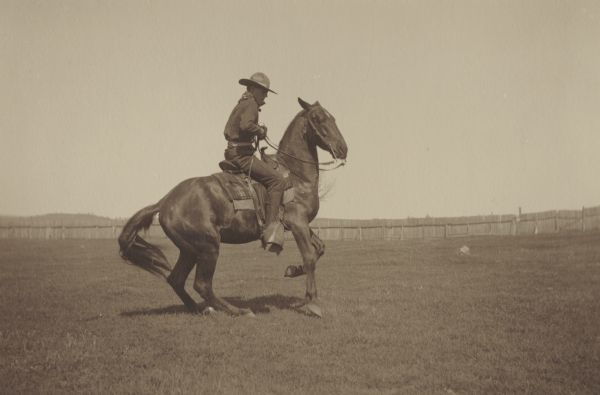 George E. Thompson, member of the Menomonie High School class of 1905, depicted as a cowboy. Pictured riding a horse and wearing a cowboy hat. Part of a yearbook created by classmate Albert Hansen, based on a class prophecy theme.