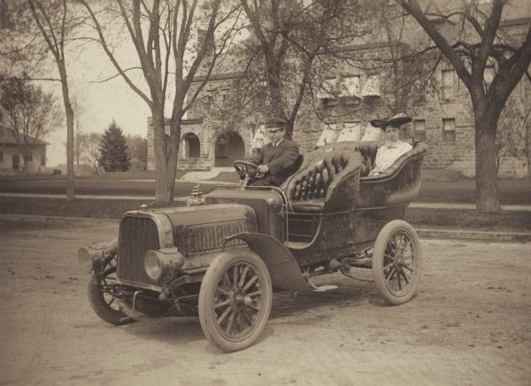 Alice M. Tilleson, member of the Menomonie High School class of 1905, depicted as a prominent socialite. Pictured being escorted in the back of an automobile. Part of a yearbook created by classmate Albert Hansen, based on a class prophecy theme.