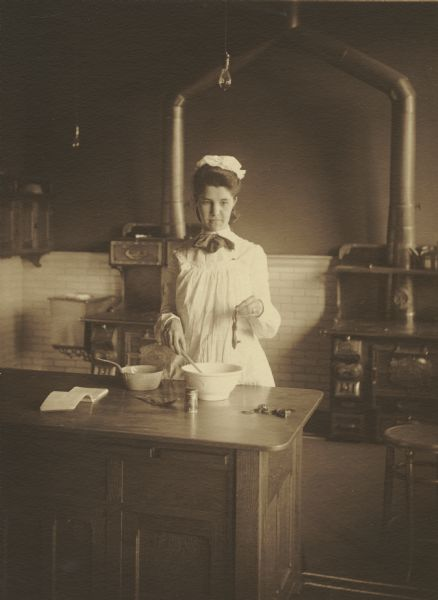 Bertha L. Retelsdorf, member of the Menomonie High School class of 1905, depicted as a cook . Part of a yearbook created by classmate Albert Hansen, based on a class prophecy theme.