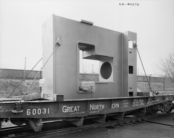 "A seamless pipe fitting sits atop a railroad car, ready to be shipped. Later purchased and used by Elmes & Kings. Original Falk caption reads, ""14' high-78,000 pound rgh unit."""