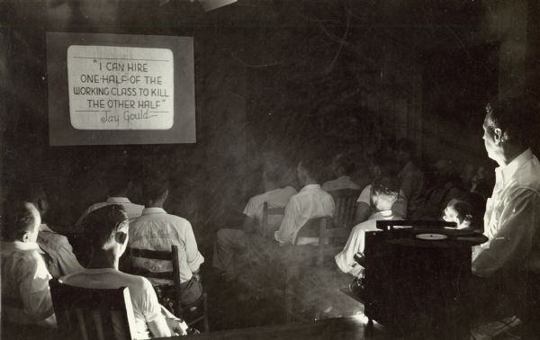 "A movie being shown at Highlander Folk School.  Still frame reads, ""I can hire one-half of the working class to kill the other half,"" a Jay Gould quote.  Gould was a famous American railroad developer and speculator."