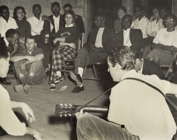 Music being played at a Highlander Folk School student workshop. John Lewis in back, extreme left; James Bevel, kneeling, left (in front of John); Candie Anderson (Carawan), 4th from right in rear.