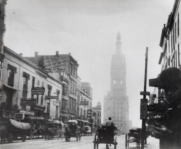 Street view; City Hall is in background.  Taken on the edge of a street with horse-drawn carriages, and buildings lining the street, and a man wearing a hat in the bottom right corner.
