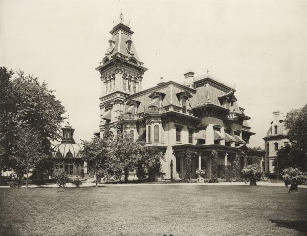 House at Ninth Street and Grand Avenue.  A large lawn is in the foreground.  The main building is centered with a tower on the left corner.  Separate buildings, including a greenhouse with a domed roof, are on either side of the house.