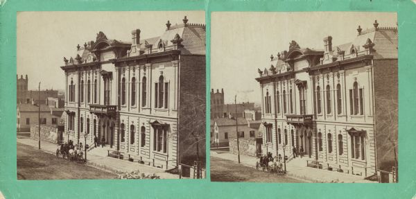 Stereograph; front of music hall along the road, with a horse and carriage team in front of the entrance.  Buildings can also be seen in the left background.