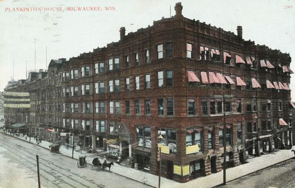 View looking east on Grand Avenue from the corner of Grand Avenue and 2nd Street. Plankinton Block was located between West Water (now Plankinton Street) and N. 2nd. It housed Plankinton House Hotel until 1915. The top two floors on the right have red and white stripped awnings over the windows. The bottom two floors have advertising signs in many of the windows.  A horse and cart is sitting on the left.
