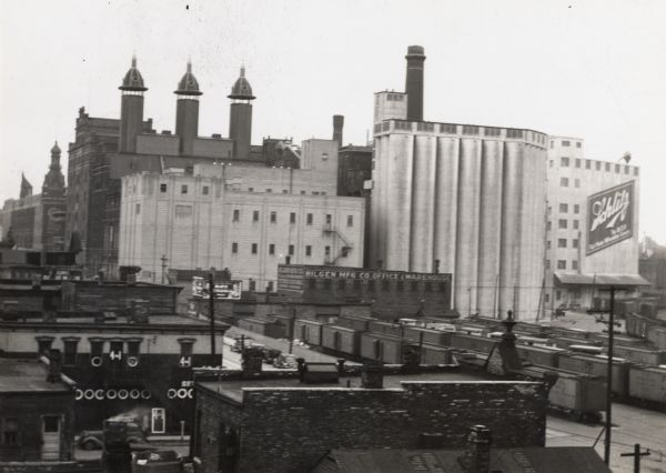 "There is a sign painted on a building at right that reads ""Schlitz"". In the bottom right are railroad cars."
