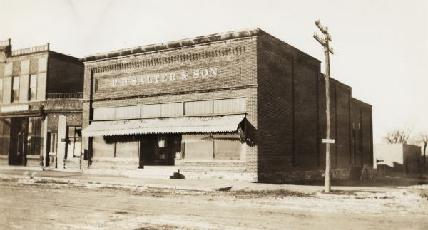 "View across road of two-story brick building with a small awning over the front.  Located on the corner of a dirt road.  The awning has ""General Merchandise"" written on the top, and the letters placed on the second floor read ""R.B. Salter & Son."""