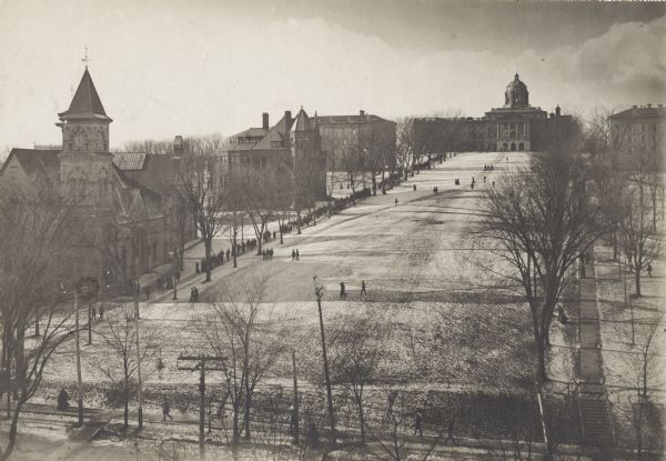Elevated view of Bascom Hill and lower campus vicinity from the roof of the Wisconsin Historical Society, which was then under construction. A large group of pedestrians are walking on the path on the right, and there is snow on the ground. Bascom Hall (formerly Main Hall) is at the top of the hill. Music Hall with the clock tower is on the left.