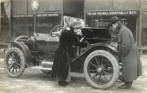 """A man and woman are looking under the hood of a car in front of a business whose sign states, """"The car that is seen and not heard. The car you will eventually buy."""""""