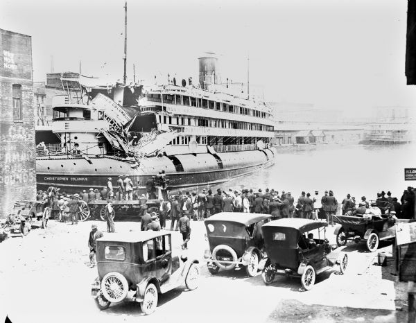 Large crowd looking at the damaged <i>Christopher Columbus</i> cruise vessel at dock. Constructed in 1893, the <i>Christopher Columbus</i> was the only passenger-carrying whaleback steamer ever built. Eighteen passengers died when the ship hit a water tower on the bank of the Milwaukee River on June 30th, 1917.