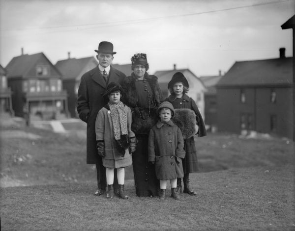 The J. Robert Taylor family. J. Robert Taylor, his wife Alma Reinhardt Taylor, and their three children, Donna, Frederick, and Ellen. They are dressed in cold weather clothing, including, hats, gloves, and fur muffs. They stand on a lawn. Behind them are houses in a row along a street.