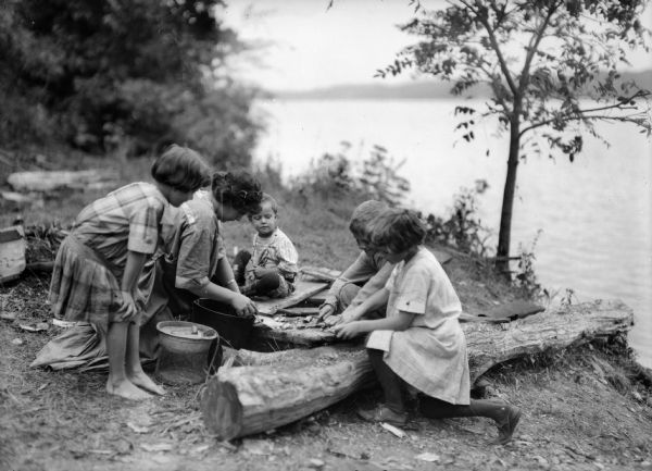 The J. Robert Taylor family on what appears to be a lake shore, possibly cleaning fish. From left: Donna Taylor Adams, Alma Reinhardt Taylor, Fred Taylor, Robert Taylor, and Ellen Taylor Higgins.