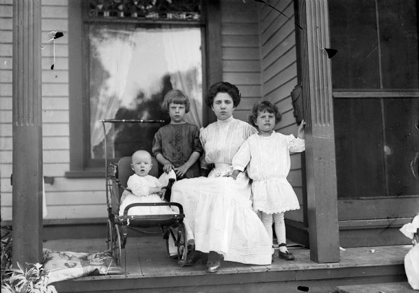 Mother and children on front porch.  Identified as Fred Taylor in the baby carriage, Ellen Taylor Higgins, Alma Reinhardt Taylor, and Donna Taylor Adams.