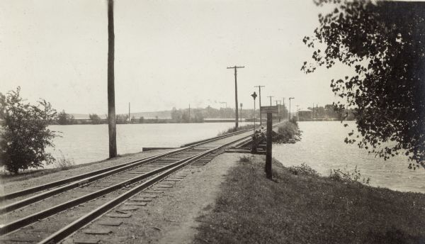 "Looking southwest along the Chicago, Milwaukee & St. Paul Railroad causeway.  Two boys fish from the bridge.  The sign declares ""Private Property.  No Thoroughfare.  Keep Off.""  The Chicago & North Western Railroad track is in the background."