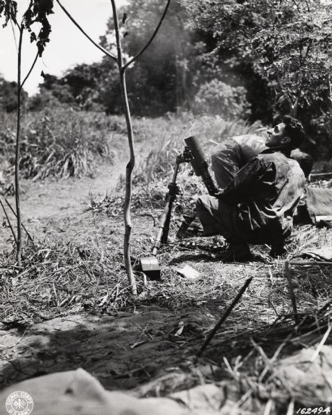 Sergeant Peter Merkel, a member of the 32nd Division from Milwaukee, firing a mortar somewhere in New Guinea.