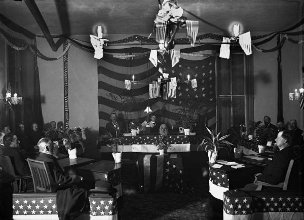 Men gather at lodge hall, probably in Watertown, Wisconsin. American flags are hanging from the light fixtures, draped over tables and on the wall. There is a man sitting with his head just above a hole in a table at the front of the room. The other men are sitting in chairs in front of small tables around him.