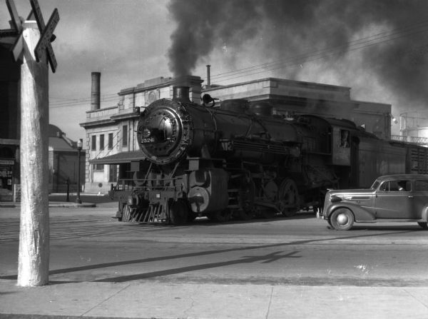 A train is shown at the intersection of Williamson, S. Blair, and E. Wilson Streets in front of the Chicago and Northwestern Railroad Depot.