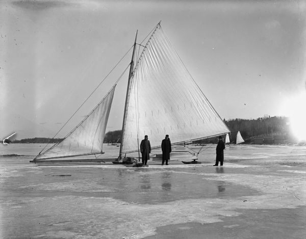 Three men stand near a large iceboat owned by Dutton and Wheeler on Lake Mendota.