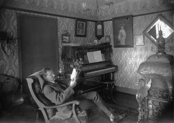 Otto G. Ansorge sits in his home on Lake Avenue and reads. Ansorge was a jeweler and band director in Winneconne.