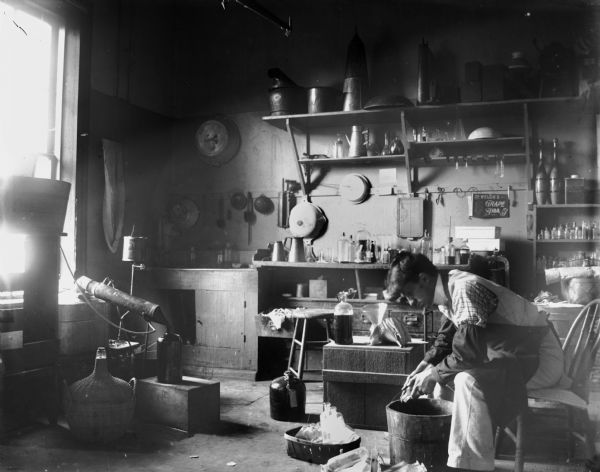 A man scrubs bottles in the back workroom of the Brennecke and Bergmann Pharmacy. Various other bottles and utensils are visible in the background.