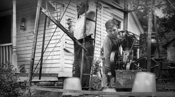 A young boy in overalls operates a machine, perhaps a pump for water, underneath a windmill. There are overturned buckets in the foreground. An elderly man stands on the left next to a ladder on the windmill smoking a cigar. They are near the front porch of a house.