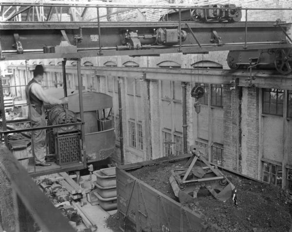 "View near crane operator looking down on coal car near exterior of building. Pawling & Harnischfeger type ""O"" bridge crane with a type ""G"" trolley in a foundry operation unloading a coal car with a grab bucket unit. The crane is stamped ""Patented, Pat. No's., 647436, 697393."" The man is operating the dial controls of the cab."