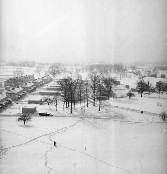 Elevated winter scene of Greendale (Milwaukee Co.), Wisconsin. Housing, roads and trees are visible in the distance. One person is walking through the snow in the foreground, and on the road behind is a snowplow on a road.