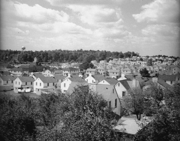 Elevated view over trees of village. In the background is a water tower on a hill with trees.