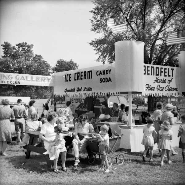 "A scene from the Greendale Civilian Defense Rally. Mothers and children sit at a picnic table outside of the ""Bendfelt House of Fine Ice Cream"" stand operated by the ""Greendale Girl Scouts."" The ice cream stand is situated next to the ""Shooting Gallery Rifle Club."""