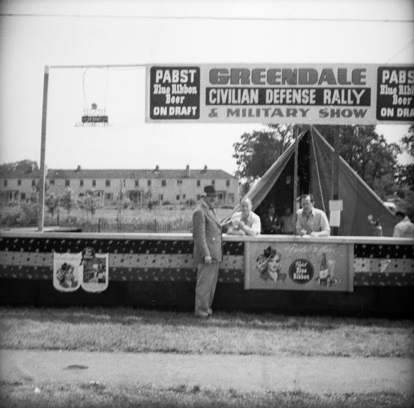"A man orders a beer from the outdoor bar at a Civil Defense Rally. The banners on the booth read ""Pabst Blue Ribbon Beer On Draft"" and ""Greendale Civilian Defense Rally & Military Show."" There is a tent in the background."