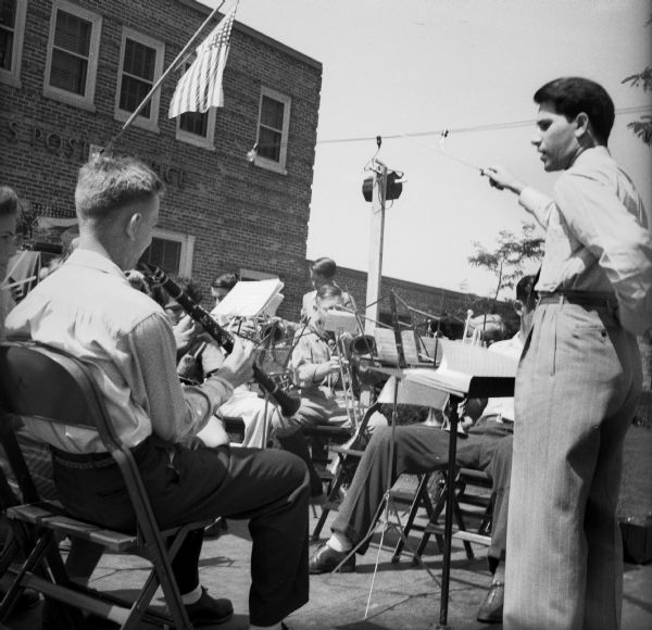 A conductor leads a band made up of school-age children as well as a few adults at a Civilian Defense Rally. They are playing outdoors in front of the Post Office.