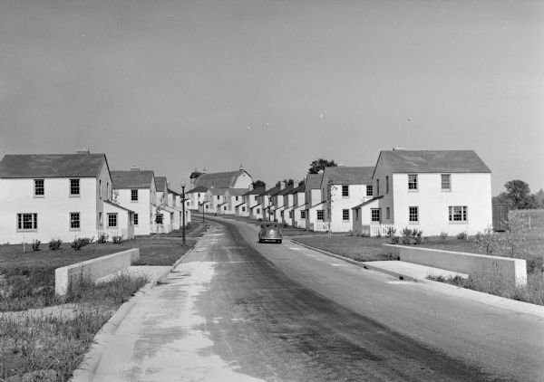 View down road of mass-produced residential housing with farm in background.