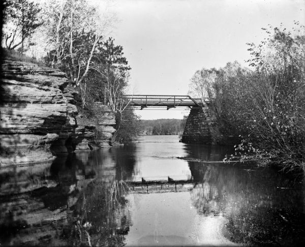 View from river of Dell Creek bridge with bluff and birch trees on the left.