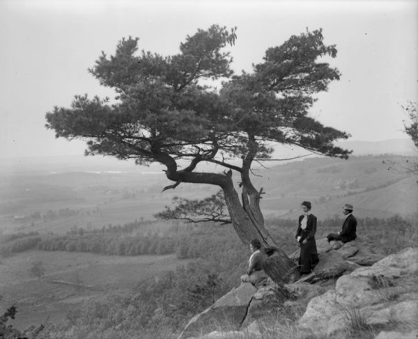 Two women and a man pose atop Gibraltar Rock in Richmond Memorial Park, which was dedicated by Jens Jensen and the Wisconsin Friends in 1927 in order to conserve the native landscape. The Wisconsin River is visible in the background.