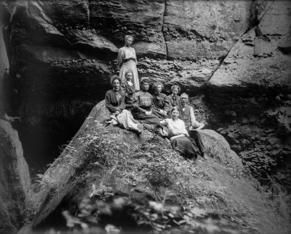Seven women and a man pose on a large boulder in front of a wall-like rock formation probably in Parfrey's Glen.