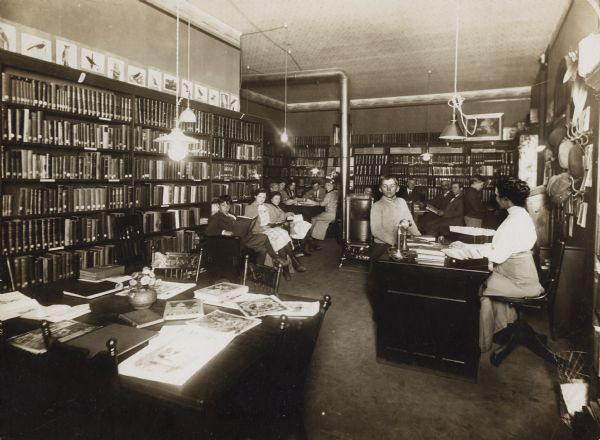 "Interior view of the Brodhead Public Library. The back of the cardboard mounting reads: ""Free Public Library, Brodhead, Wis."" There is a stove in the center of the room. A woman (librarian?) is seated at a librarian's desk, and there are hat hooks and hats on the wall. Bookshelves line the walls, and a group of children and adults are using the room."