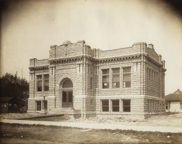 "Exterior view of the Sturgeon Bay Public Library. Library opened in 1913 with a gift of $12,500 from Andrew Carnegie. Above the main entrance it reads: ""Free Library."" The stone building has an arched entrance. There is construction debris and unfinished landscaping around the building."