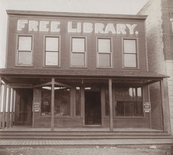 "Exterior view of the Wausaukee Public Library. Above the windows on the second floor is painted: ""Free Library"" in large letters. Two signs advertise: ""Booth's Oysters."" The wooden two-story building has an open porch. There is a restaurant on the first floor.  Additional notes from ""Some Wisconsin Library Buildings, 1904."" Established 1902. 1,000 volumes. This ""social hall"" was given by Hon. H. P. Bird as an attempt at the solution of the social problem of a small lumber town. The building contains library, reading-room. lunch and dining room, and amusement room."