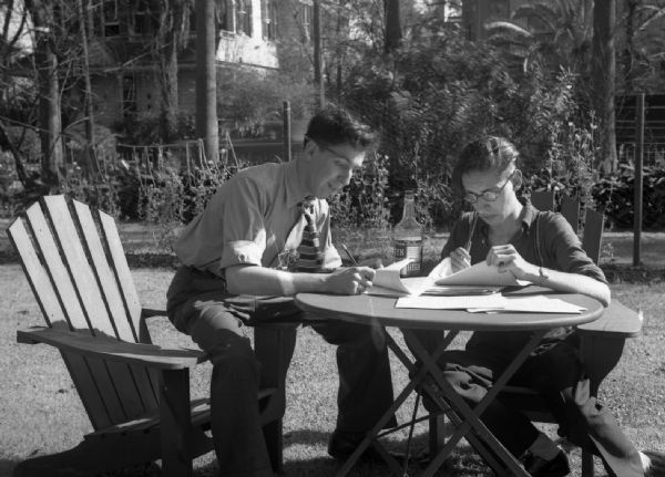 Harold Gauer and Robert Bloch sit on chairs outside in a backyard writing on sheets of paper. A liquor bottle sits on the table between them.