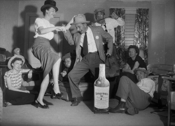 A couple dances behind an oversized cut-out of a bottle of Seagrams Whiskey, with other people seated around them. Some are wearing fake eyes.